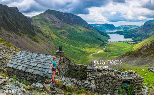 woman trail runner overlooking mountain valley bothy lake district panorama - national park stock pictures, royalty-free photos & images