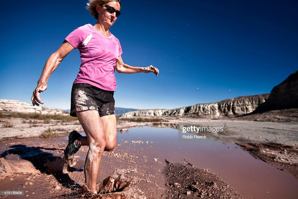 A woman trail runner races through mud and water : Stock Photo