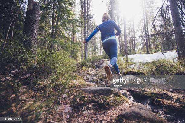 woman trail runner running in forest. - running stock pictures, royalty-free photos & images