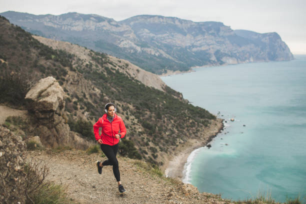 Woman trail running in mountains with scenery view of sea and coastline. Active and healthy lifestyle