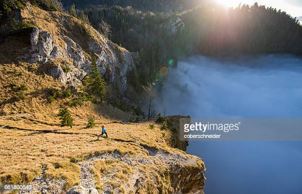 Woman Trail Running in the Mountains above the Clouds, Salzburg, Austria