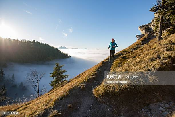 woman trail running in the mountains above the clouds, salzburg, austria - cross country running stock pictures, royalty-free photos & images