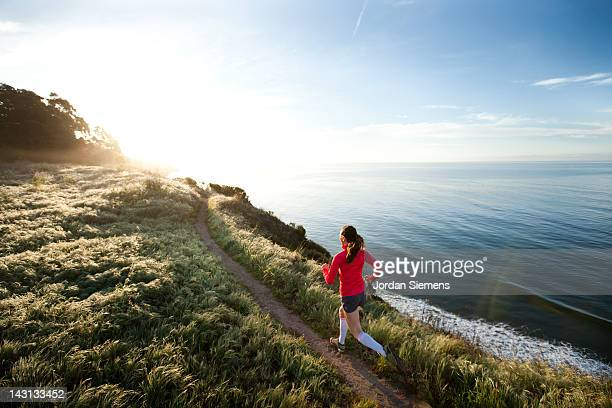 woman trail running near the ocean. - southern california stock pictures, royalty-free photos & images