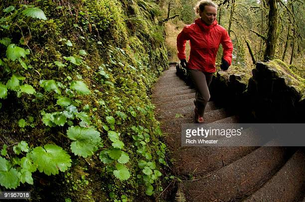 A woman trail running up stairs through a green, mossy forest in Silver Falls State Park, Oregon, US
