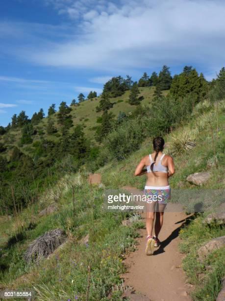 woman trail runs mount falcon morrison colorado front range rocky mountains - front range mountain range stock pictures, royalty-free photos & images