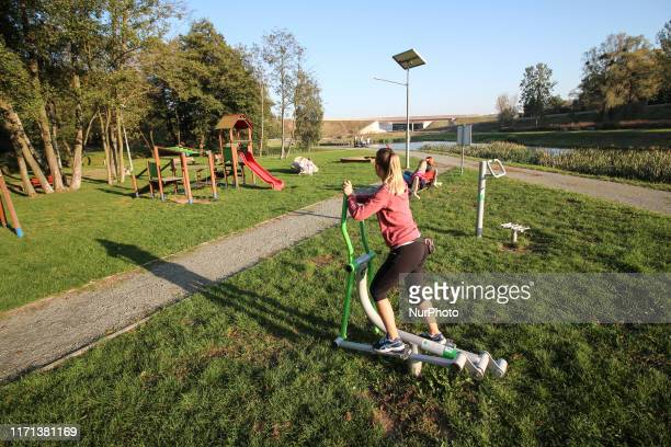 Woman training in a public openair gym on a recreation area near a children's playground in Gdansk Kielpinek district Poland on 26 September 2019...