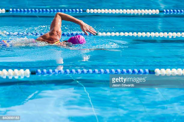 A woman training in a swimming pool doing laps.