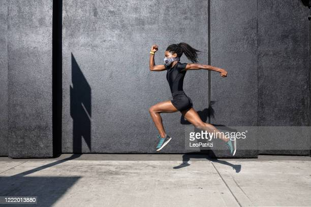 woman training in quarantine using a face mask - sportsperson stock pictures, royalty-free photos & images