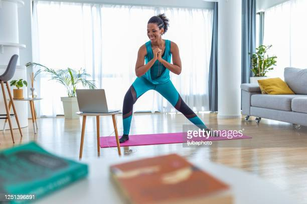 woman training indoors doing side lunges working out legs, hips and buttocks - beautiful female bottoms stock pictures, royalty-free photos & images