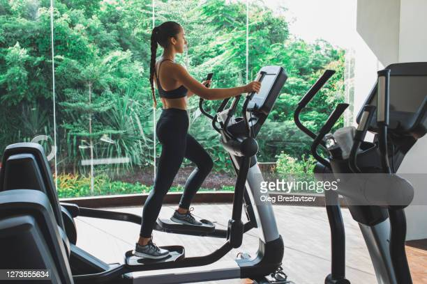 woman training on stepper or treadmill in fitness club of gym. side view. power and endurance functional cardio training. woman health. - peloton stock pictures, royalty-free photos & images