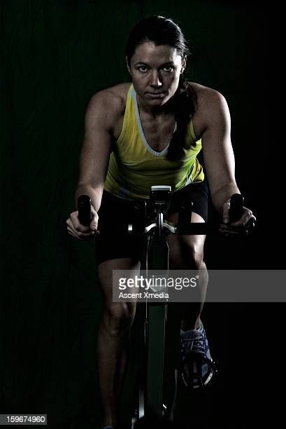 Woman trains on stationary bucycle, in gym