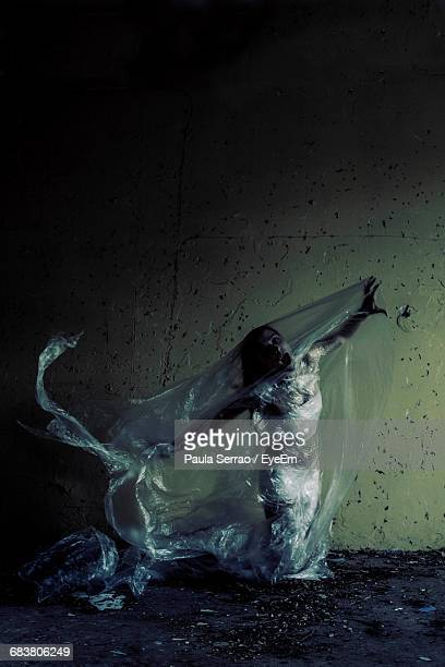 Woman Trapped In Plastic Against Wall Of Abandoned Building