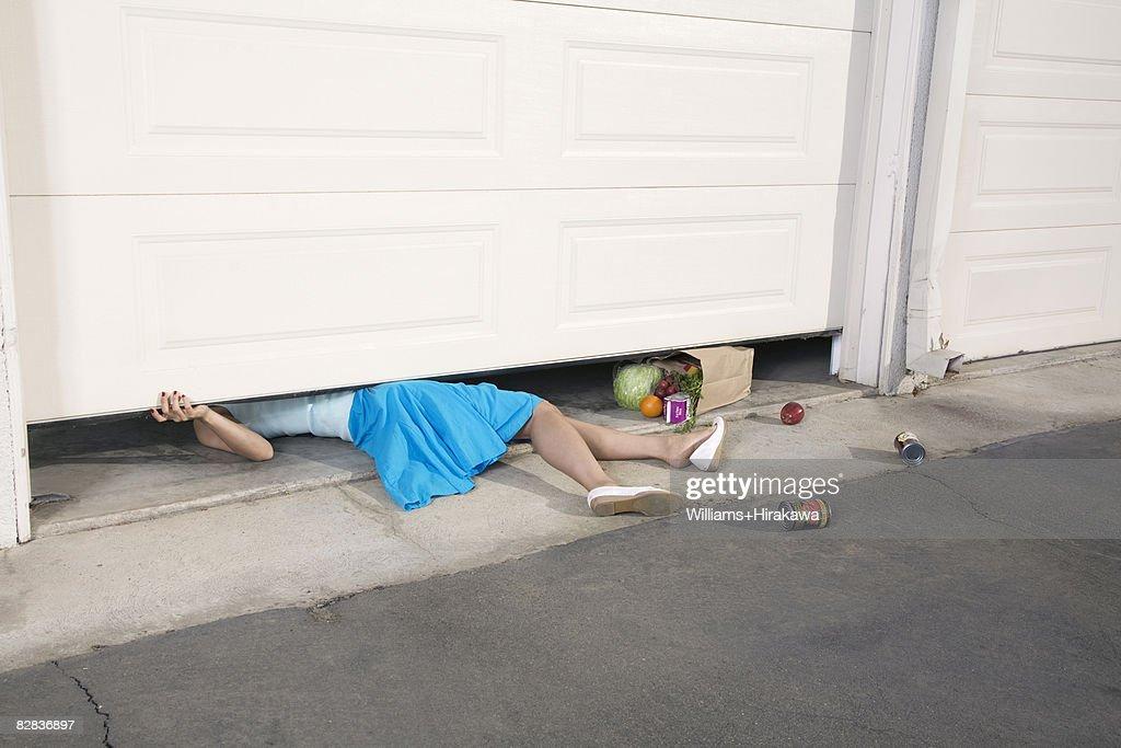 Woman trapped under garage door : Stock Photo