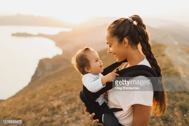 woman travel and hike with toddler baby in sling. active lifestyle - lifestyle stock pictures, royalty-free photos & images