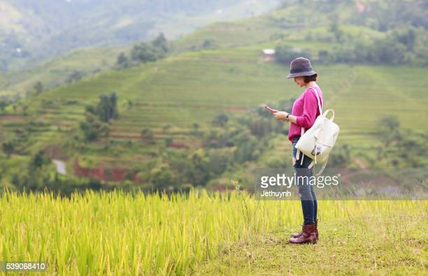 Woman traveler checkin with pad in hand among rice terraces