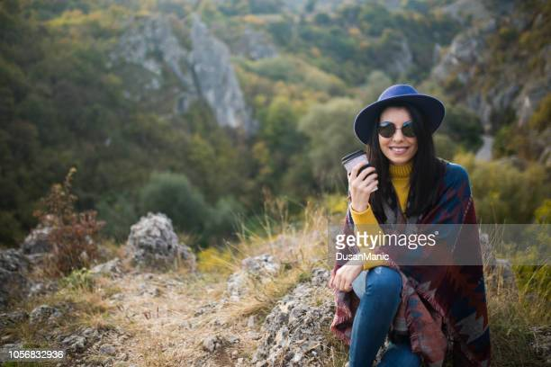 woman traveler drinks coffee with a view of the mountain landscape. a young tourist woman drinks a hot drink from a cup and enjoys the scenery in the mountains. trekking concept - coffee drink stock pictures, royalty-free photos & images