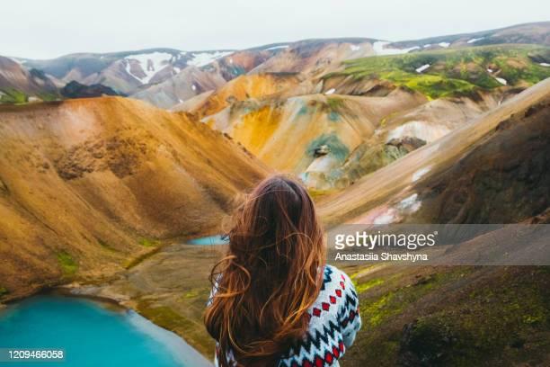 viaggiatore donna godendo della vista di pittoresche montagne arcobaleno colorate e lago turchese nel deserto - islanda foto e immagini stock
