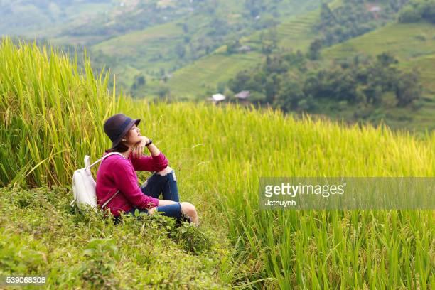 Woman traveler feeling happy when sitting among rice terraces