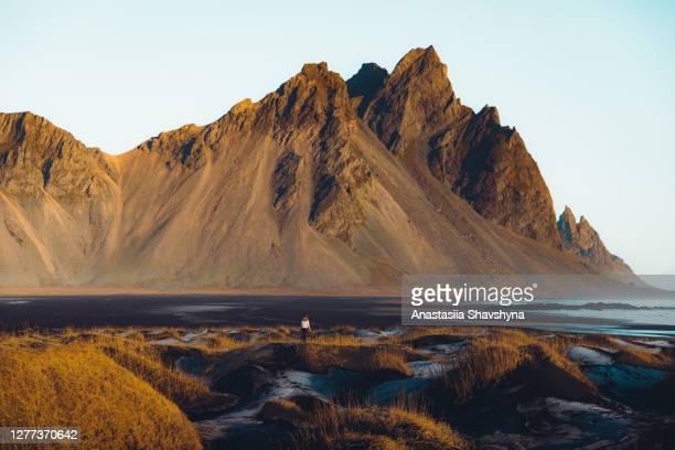 de reiziger van de vrouw ontmoet zonsopgang verabsolt het mooie zwarte strand van de zandberg in ijsland - wit hemd stockfoto's en -beelden