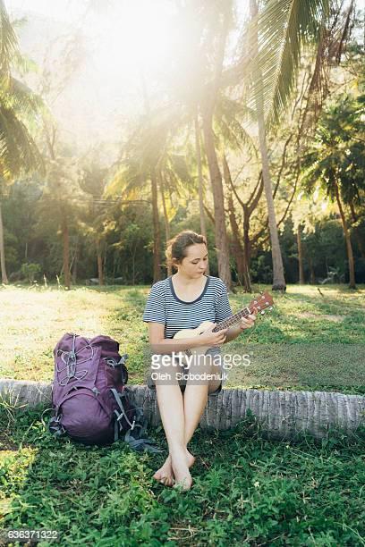 Woman traveler  playing on ukulele  near the palm trees