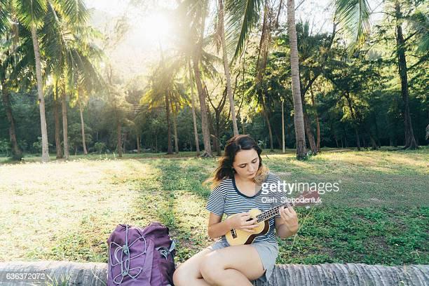 Woman traveler  playing on  ukulele