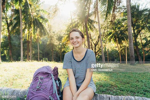 Woman traveler  sitting near the palm trees