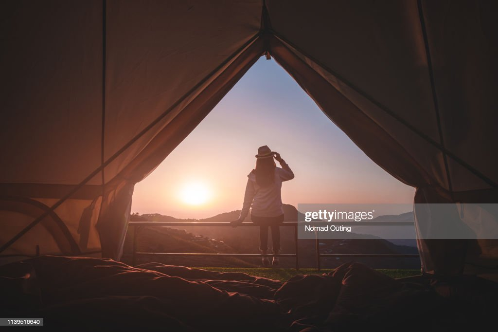 Woman traveler sitting outside camping tent and looking at sunrise view and mountain range.Travel outdoors camping for exploration and freedom concept. : Stock Photo