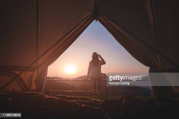 woman traveler sitting outside camping tent and looking at sunrise view and mountain range.travel outdoors camping for exploration and freedom concept. - travel fotografías e imágenes de stock