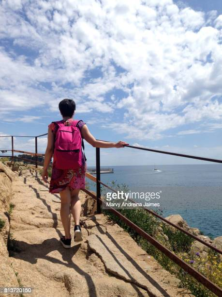 Woman traveler with backpack at Mediterranean Sea