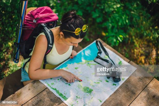 Woman traveler with backpack checks map to find directions in wilderness area, real explorer