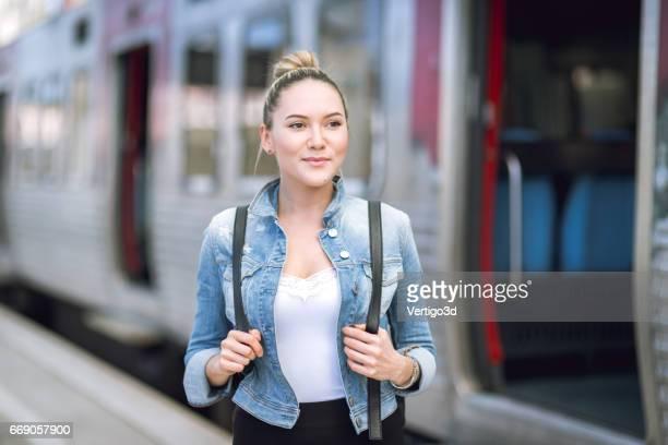Viajero mujer con mochila en la estación de tren de control de tiempo