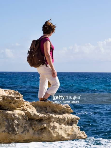 Woman traveler with rucksack and hat of straw, on a rock of a cliff looking at the sea a sunny day of blue sky. Cala of the Bergantin, Cabo de Gata - Nijar Natural Park,  Almeria,  Andalusia, Spain
