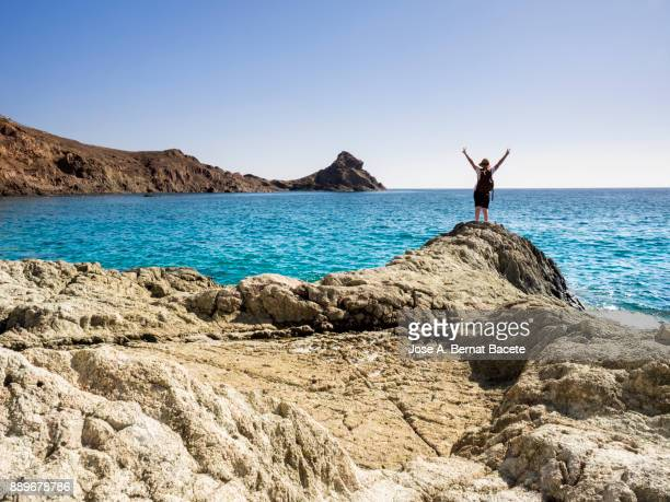 Woman traveler with rucksack and hat of straw, on a rock of a cliff looking at the sea a sunny day of blue sky. Sirens Reef, Cabo de Gata - Nijar Natural Park,  Almeria,  Andalusia, Spain