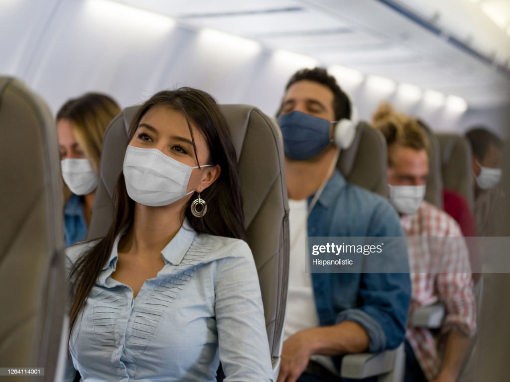 Woman traveling by plane wearing a facemask : Stock Photo