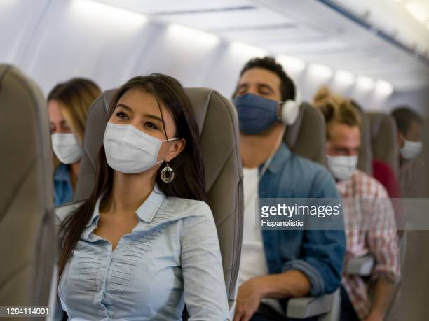 woman traveling by plane wearing a facemask - aeroplane stock pictures, royalty-free photos & images