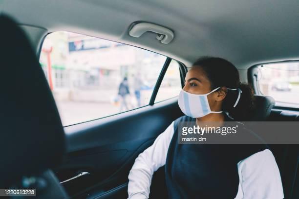 woman traveling by taxi during covid-19 pandemic - aplanar a curva imagens e fotografias de stock