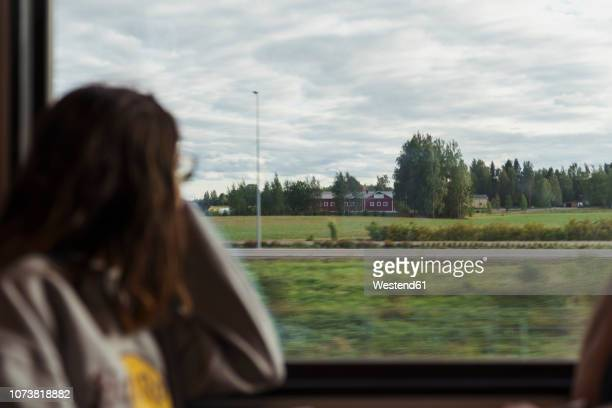 woman traveling by train looking out of window - bahnreisender stock-fotos und bilder
