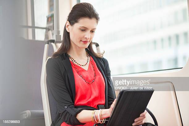 Woman traveling in a bus using a digital tablet