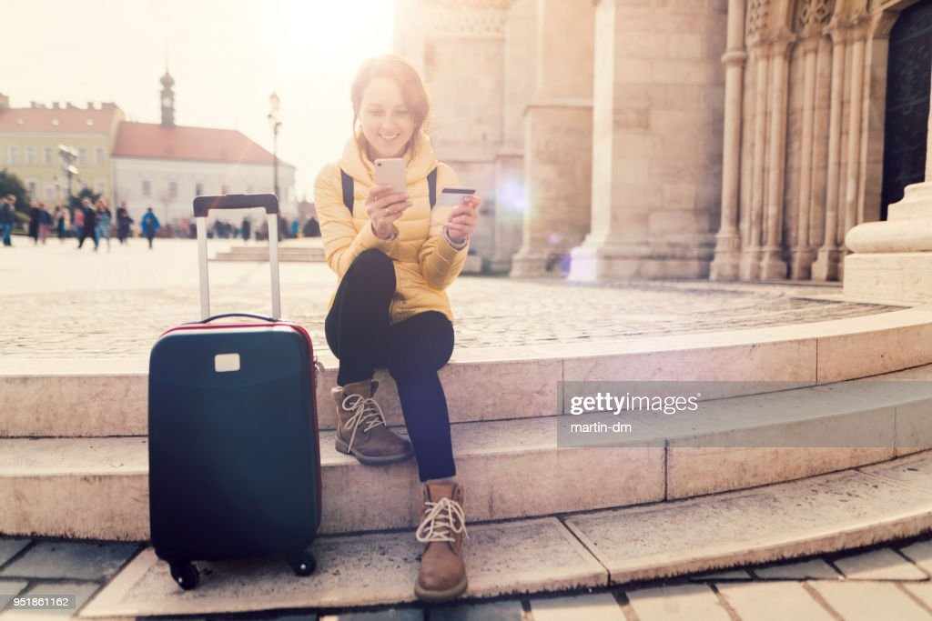 Woman traveling in Europe and using credit card for hotel reservation : Stock Photo