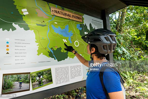 Woman traveling on a bike and looking at a map