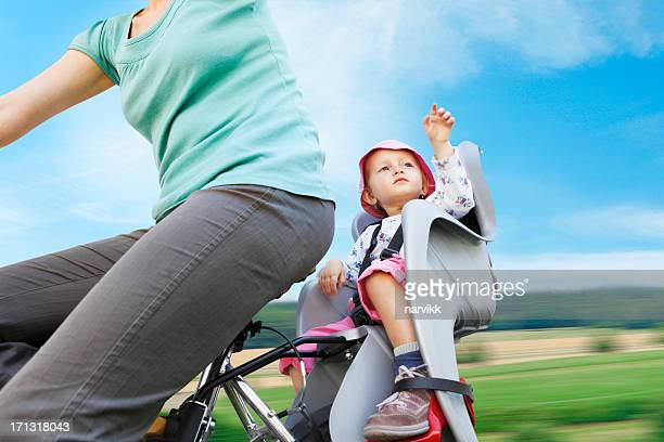 Woman traveling on bicycle with child seat