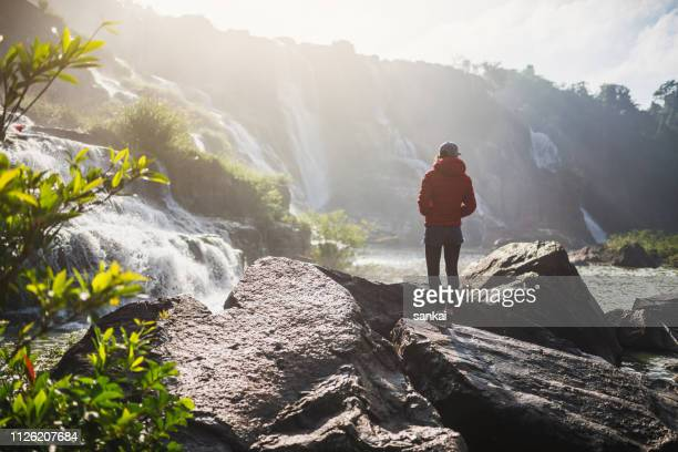 woman traveller enjoying the view of pongour waterfall in the morning. vietnam. - behind waterfall stock pictures, royalty-free photos & images