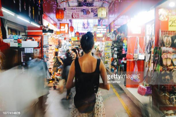 woman traveller in the busy markets of singapore - flea market stock pictures, royalty-free photos & images
