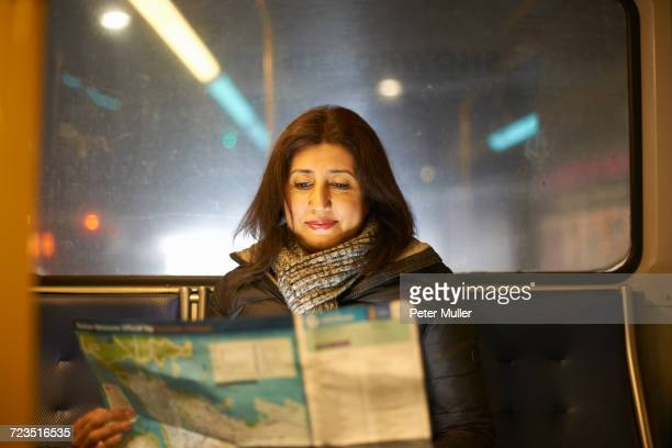 Woman travelling on bus looking at map