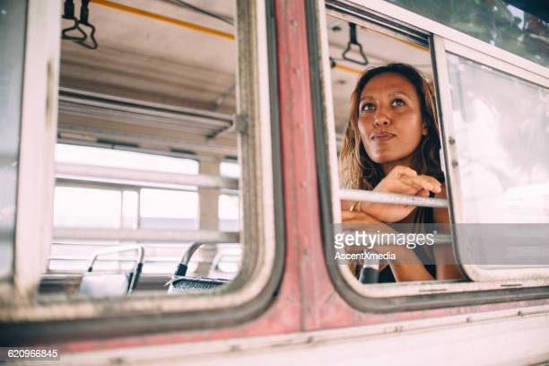 Woman travels by bus, looks out window