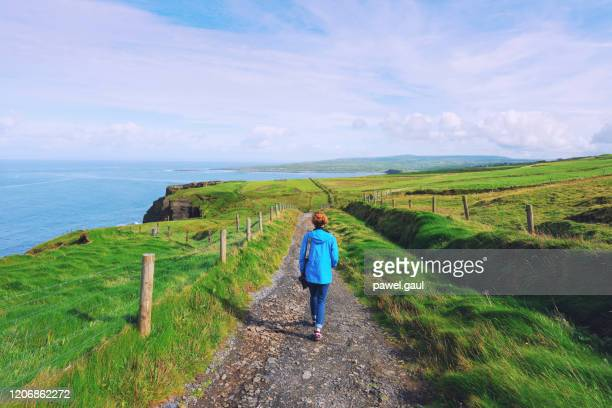 woman trekking on cliffs of moher walking trail in ireland - backpacker stock pictures, royalty-free photos & images