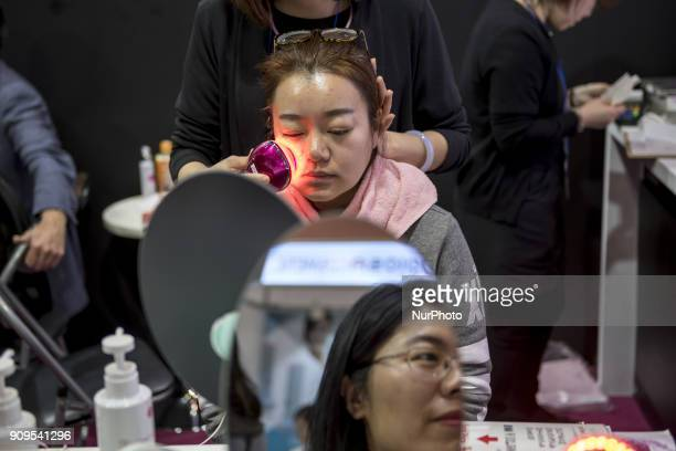 Woman tries machine for skin care during the Cosme Tokyo 2018, January 24, 2018 in Japan. Cosme Tokyo 2018 and the Asia's leading exhibition...
