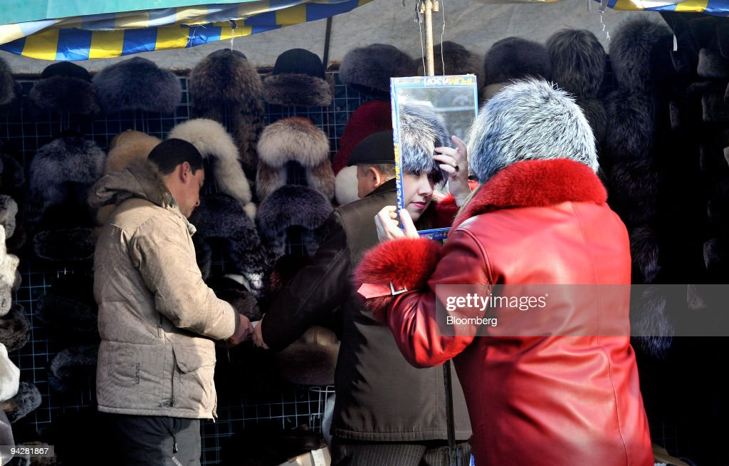 A woman tries on a fur hat at a market store in Lviev, Ukraine, on Saturday, Dec. 5, 2009. Ukraine expects the International Monetary Fund to release the next tranche of its bailout loan by the end of the year, Deputy Premier Hryhoriy Nemyria said. Photographer: John Guillemin/Bloomberg via Getty Images