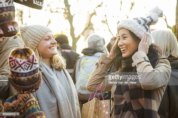 Woman tries on a hat while friend looks on, at a christmas market stall.