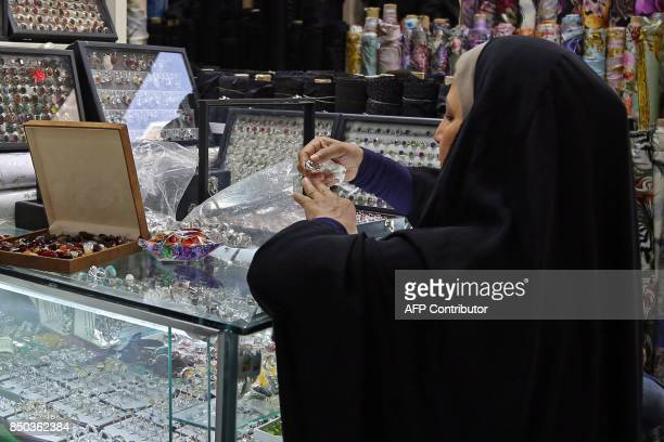 A woman tries on a ring at a jeweller's in the main market of Iraq's holy city of Najaf on September 13 2017 Strategically located facing the golden...